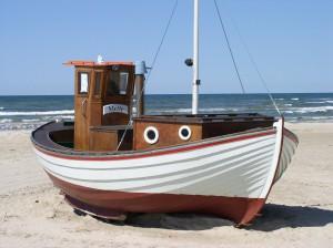 Ein Fischerboot am weißen dänischen Strand.
